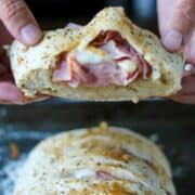 Hands holding a slice of ham and swiss braided sandwich