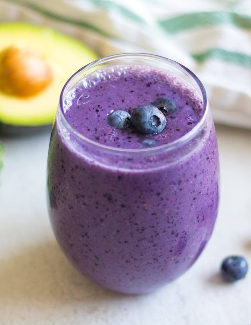 Blueberry Smoothie in glass with avocado and blueberries in background