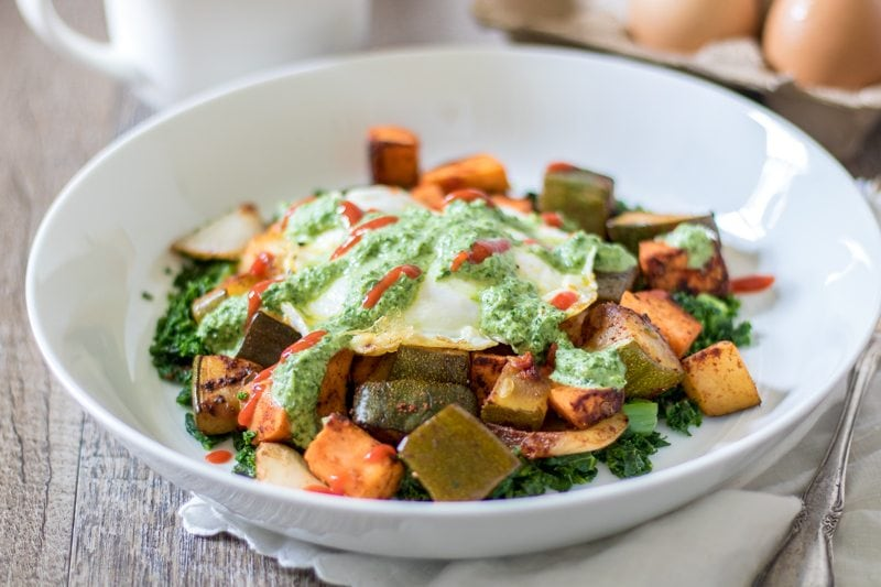 Sweet Potato hash mixed with spinach and topped with an egg in a white bowl.