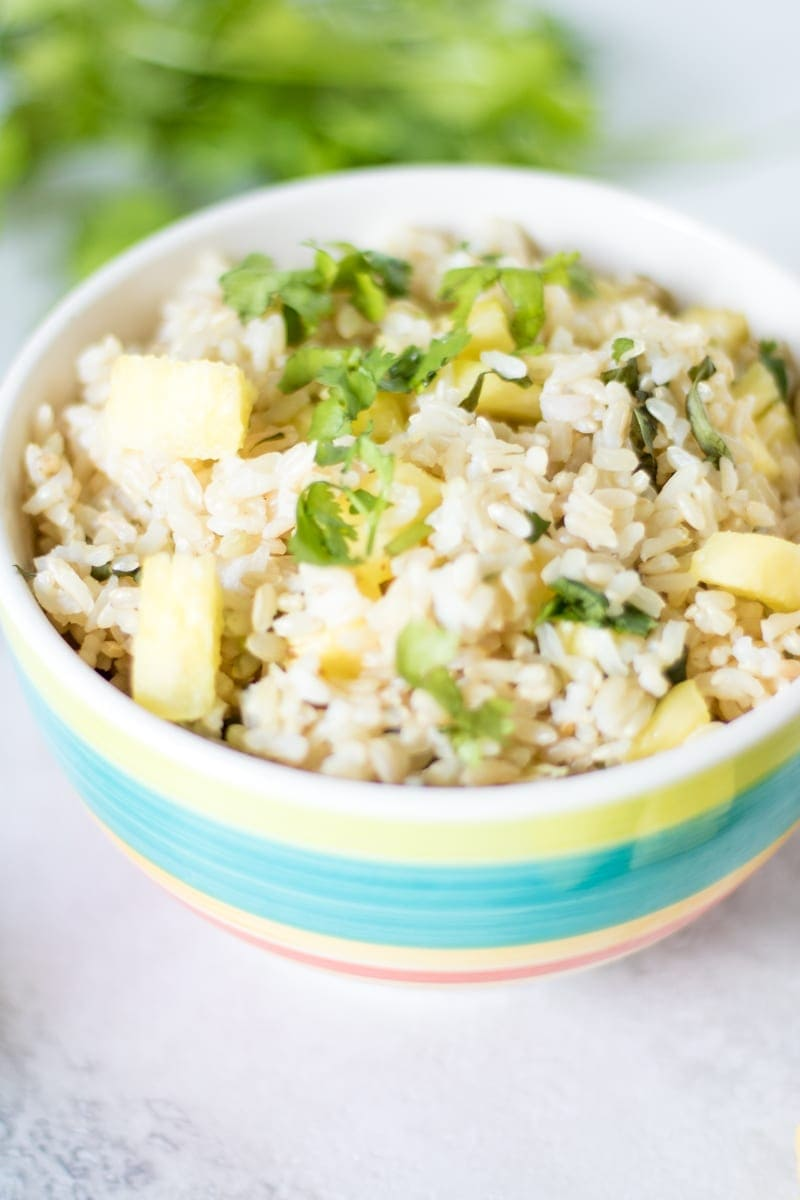 Close up of pineapple cilantro lime rice in colorful serving bowl.