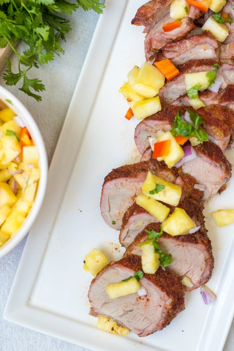 Grilled Jerk Pork Tenderloin sliced and topped with Pineapple Salsa