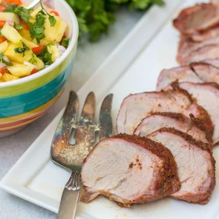 Grilled Pork Tenderloin on white platter next to pineapple salsa