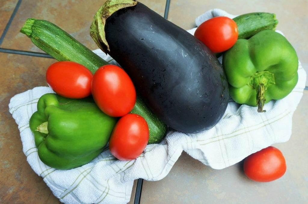 A basket lined with a towel that has an eggplant, tomatoes, 2 large green bell peppers, and a cucumber