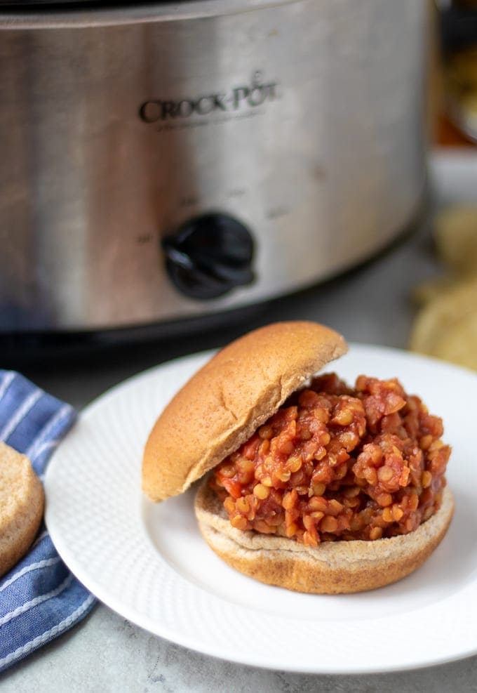 Vegan Sloppy Joe on bun next to slow cooker