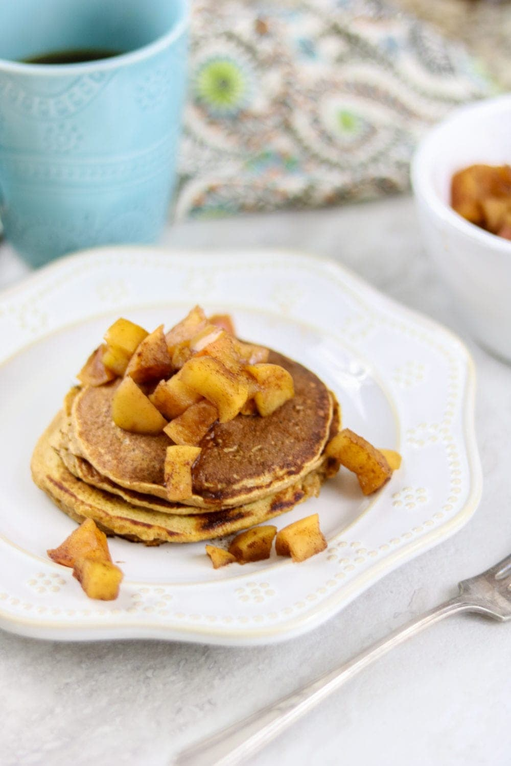 Sweet Potato Pancakes topped with spiced apples on white plate