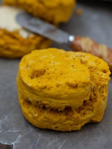 Sweet Potato Biscuit on wax paper with buttered biscuit in background
