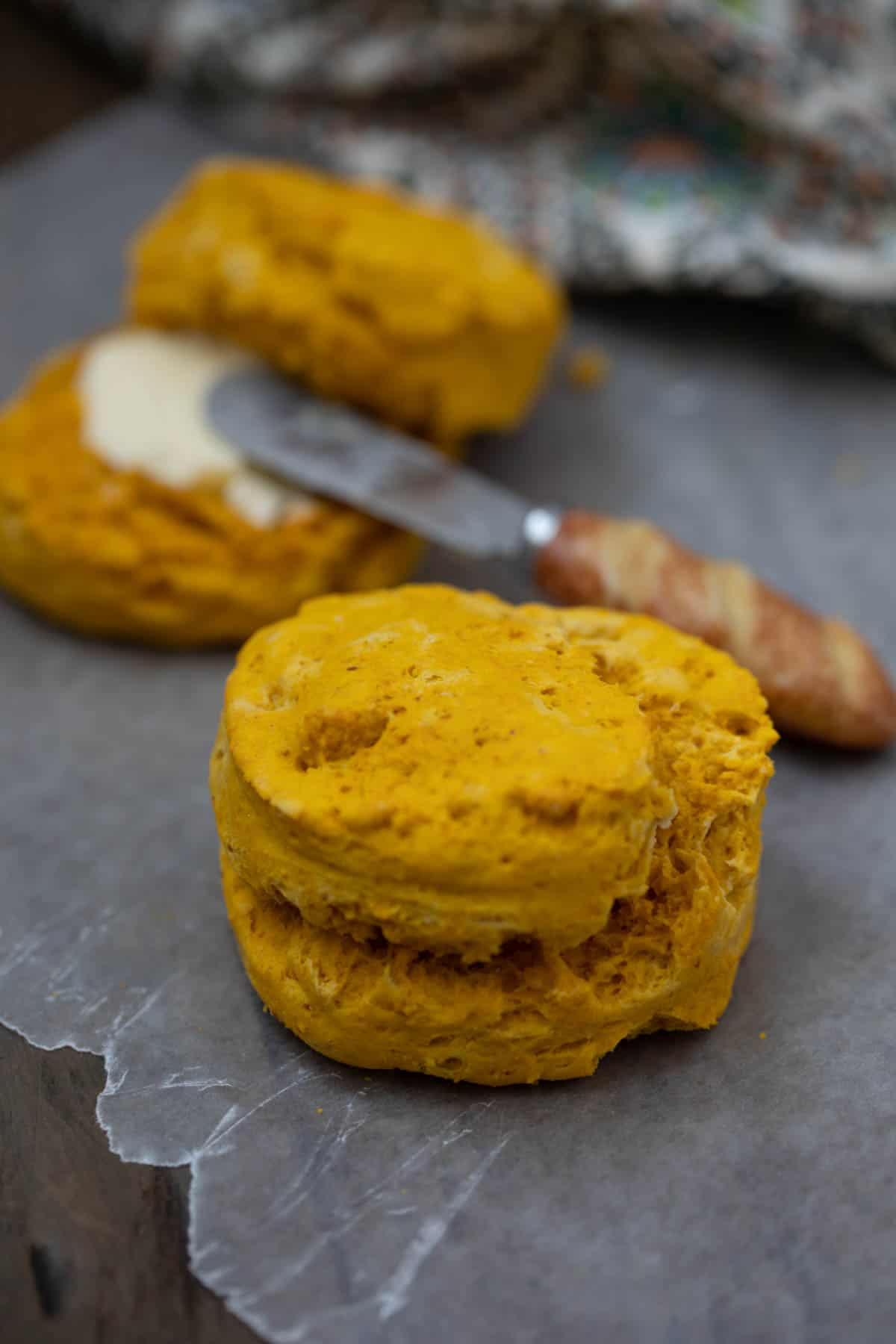 Sweet Potato Biscuit on wax paper next to biscuit with butter