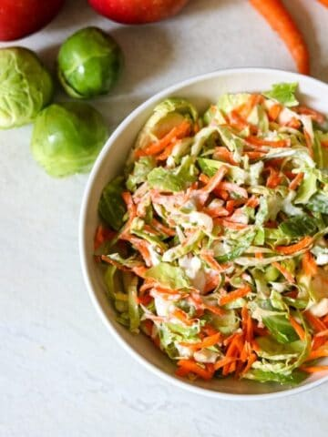 Shredded Brussel Sprout Salad with Apples in white bowl