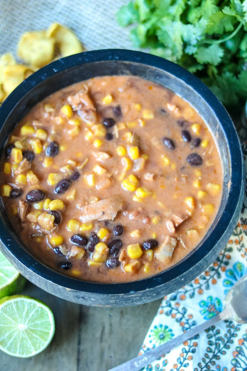 Rustic Black Bowl filled with Creamy Southwestern Turkey Soup with corn and black beans. Lime wedges and corn chips on the side of the bowl for sering.
