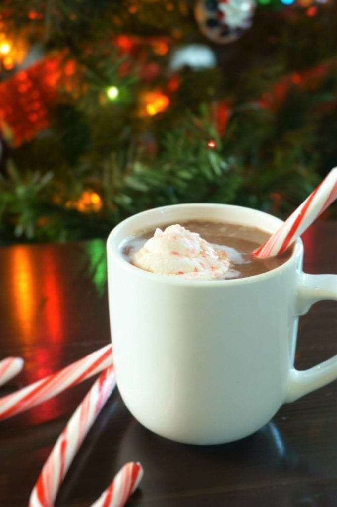 Homemade Hot Chocolate with Frozen Peppermint Whipped Cream next to lit up Christmas tree