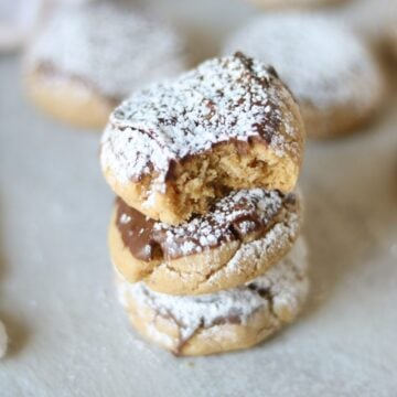 Peanut Butter Chocolate Cookies AKA Muddy Buddy Cookies: A tender peanut butter cookie is dipped in milk chocolate and then dusted with powdered sugar.