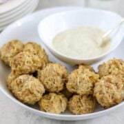 Baked sauerkraut balls in white dish with mustard sauce to the side