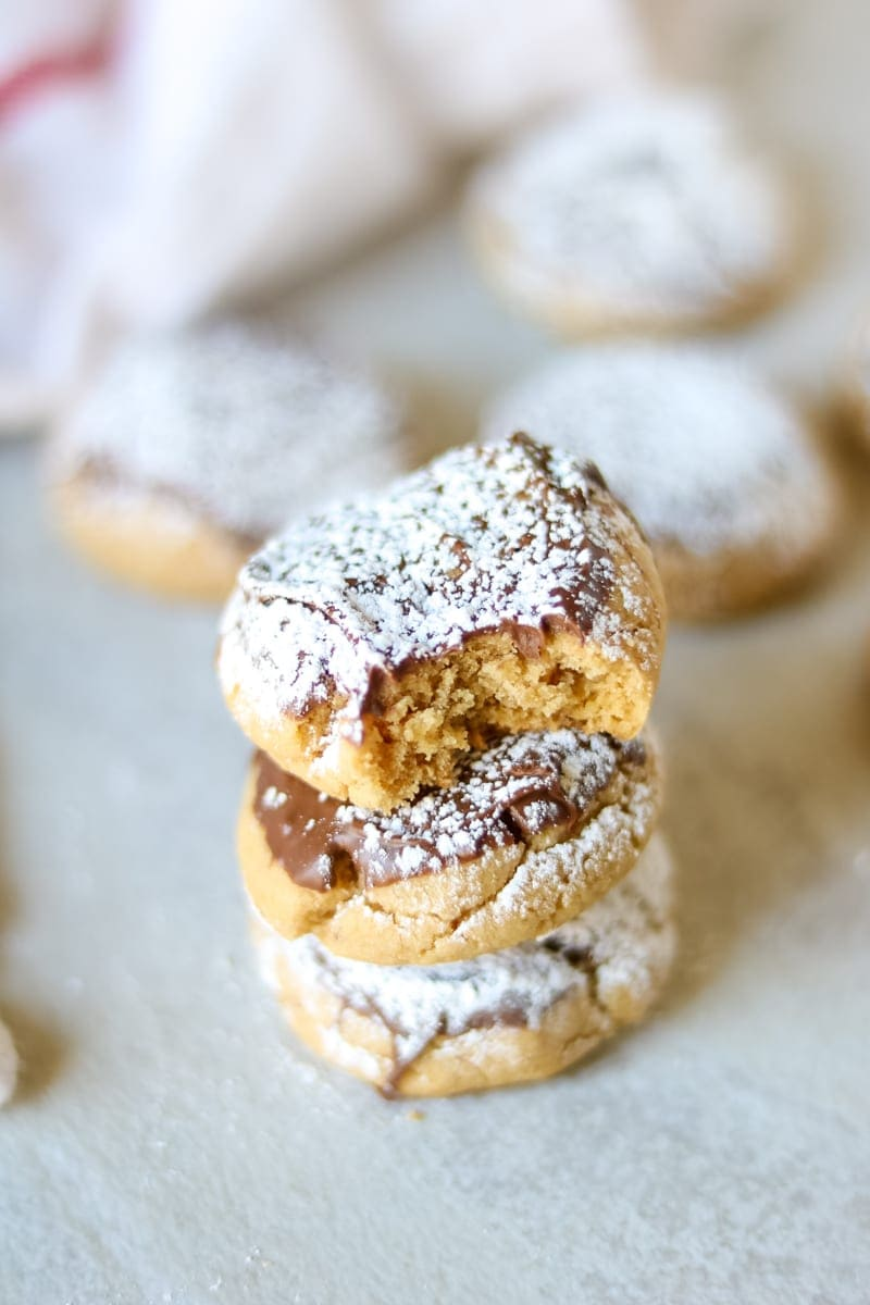 Stack of 3 Chocolate Dipped Peanut Butter Cookies dusted with powdered sugar with addtional baked cookies in the background.