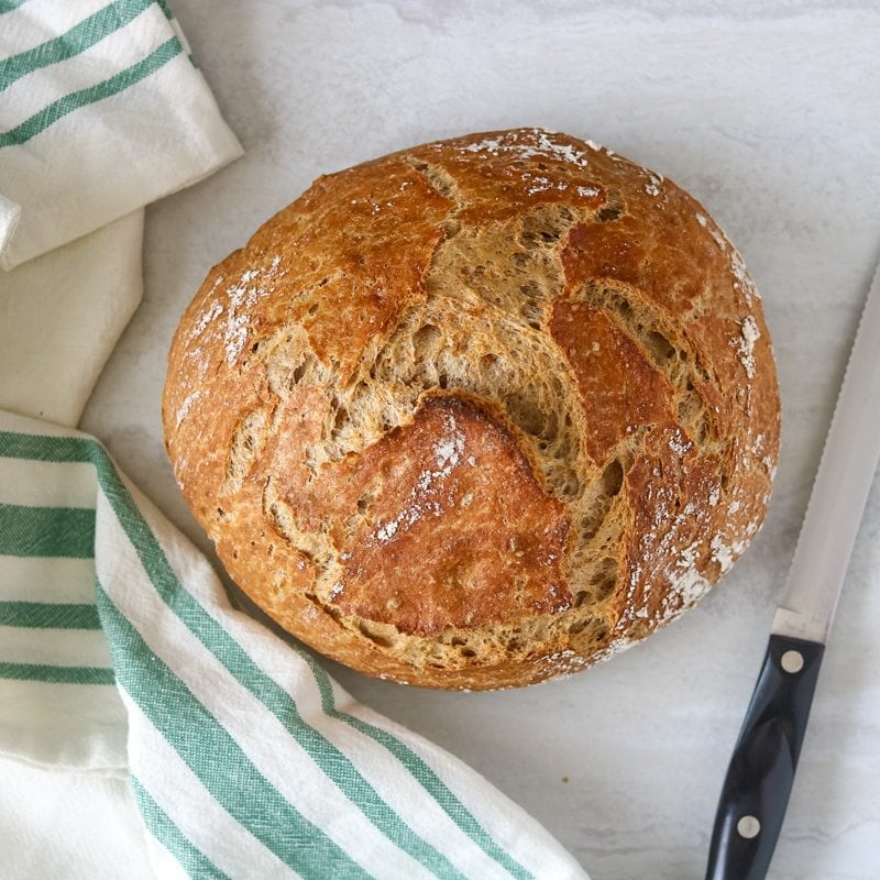Round Whole Wheat Bread on white cutting board