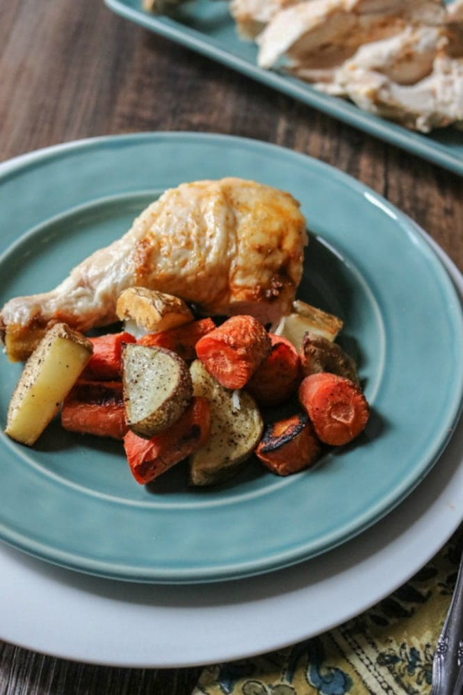 Roasted Chicken Leg on blue plate with oven roasted vegetables.