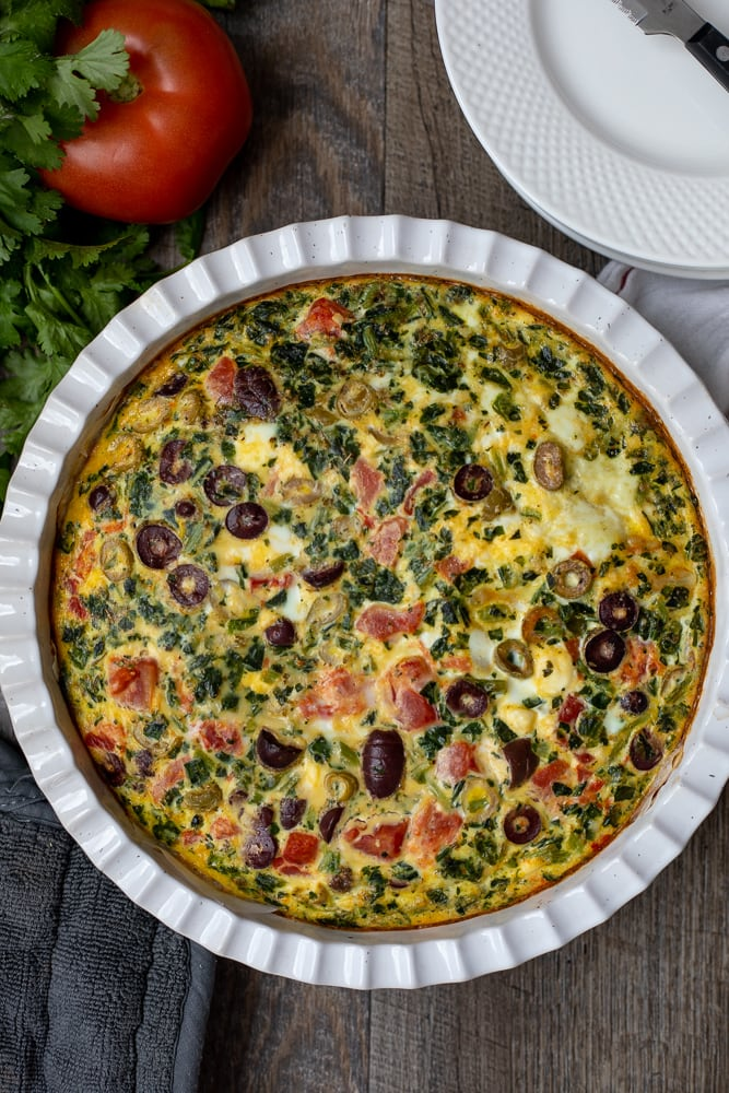 Spinach Frittata in white quiche dish next to fresh tomatoes