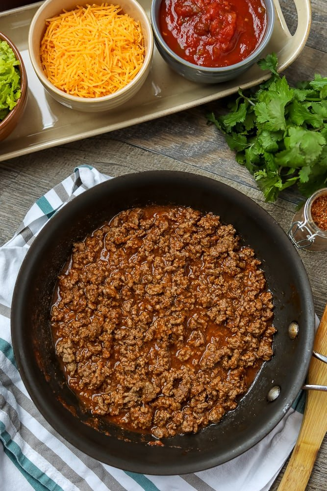 3 Ingredient Taco Meat in skillet surronded by ingredients for tacos