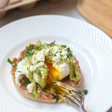 A perfectly poached egg sits upon a spicy refried beans on a toasted muffin and a creamy Avocado Hollandaise.