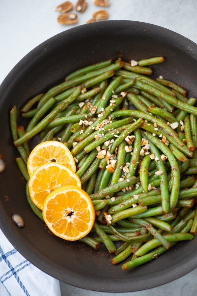 Saute pan with green beans, orange slices and pecans