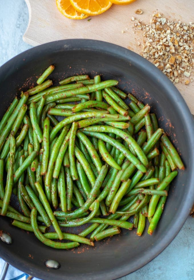 Green Beans in saute pan next to chopped nuts