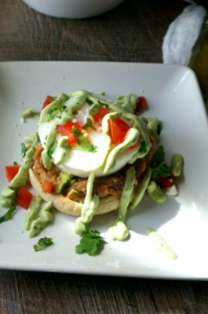 Mexican Eggs Benedict with Avocado Hollandaise: A Mexican spin to a classic. A perfectly poached egg sits upon a spicy refried beans on a toasted muffin and then finished with fresh tomatoes and a creamy Avocado Hollandaise. Served with a Mexican Avocado Salad, all made with organic avocados from ALDI.