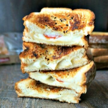 Stacked Pizza Grilled Cheese sandwiches--Cheese oozing out of Browned Garlic Bread.