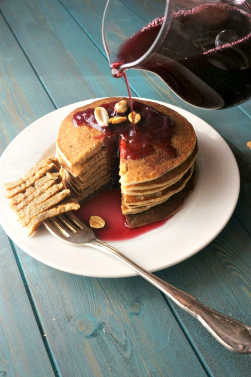 Grape Syrup being poured over peanut butter pancakes