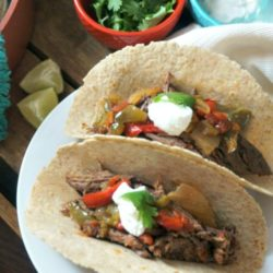 2 fajitas on a white plate filled with shredded steak and topped with sour cream
