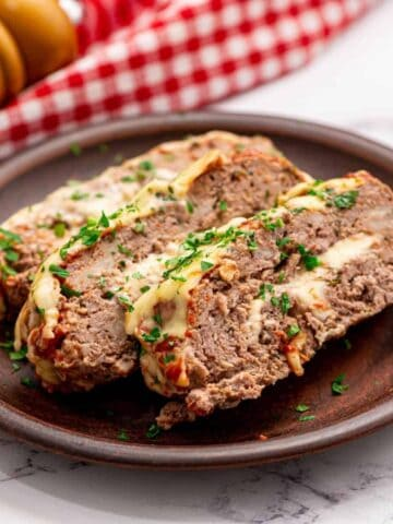 Sliced Meatloaf stuffed with cheese on top of plate.