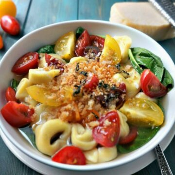 Tortellini in rich broth with spinach and tomatoes