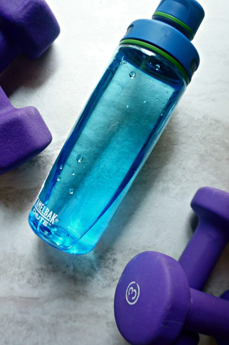 blue water bottle with purple weights on white countertop