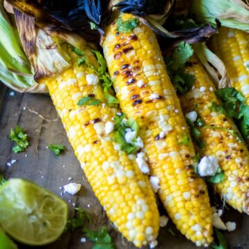 Corn on the cob with husks pulled back and seasoned with cilantro and queso fresco