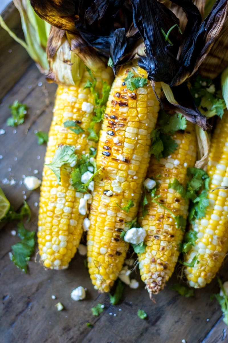 Grilled Mexican Corn: Sweet summer corn has been grilled and then tossed in a cilantro lime butter and crumbled queso fresco--for a messy, but tasty side dish.
