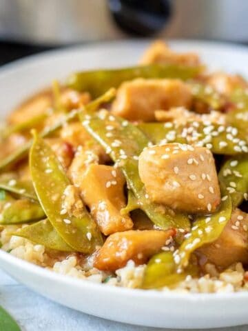 Mongolian Chicken in white bowl with snow peas and sesame seeds