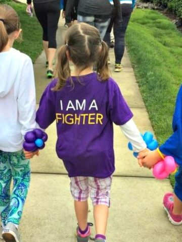 3 girls walking hand in hand with middle girl wearing shirt that says I am a fighter.