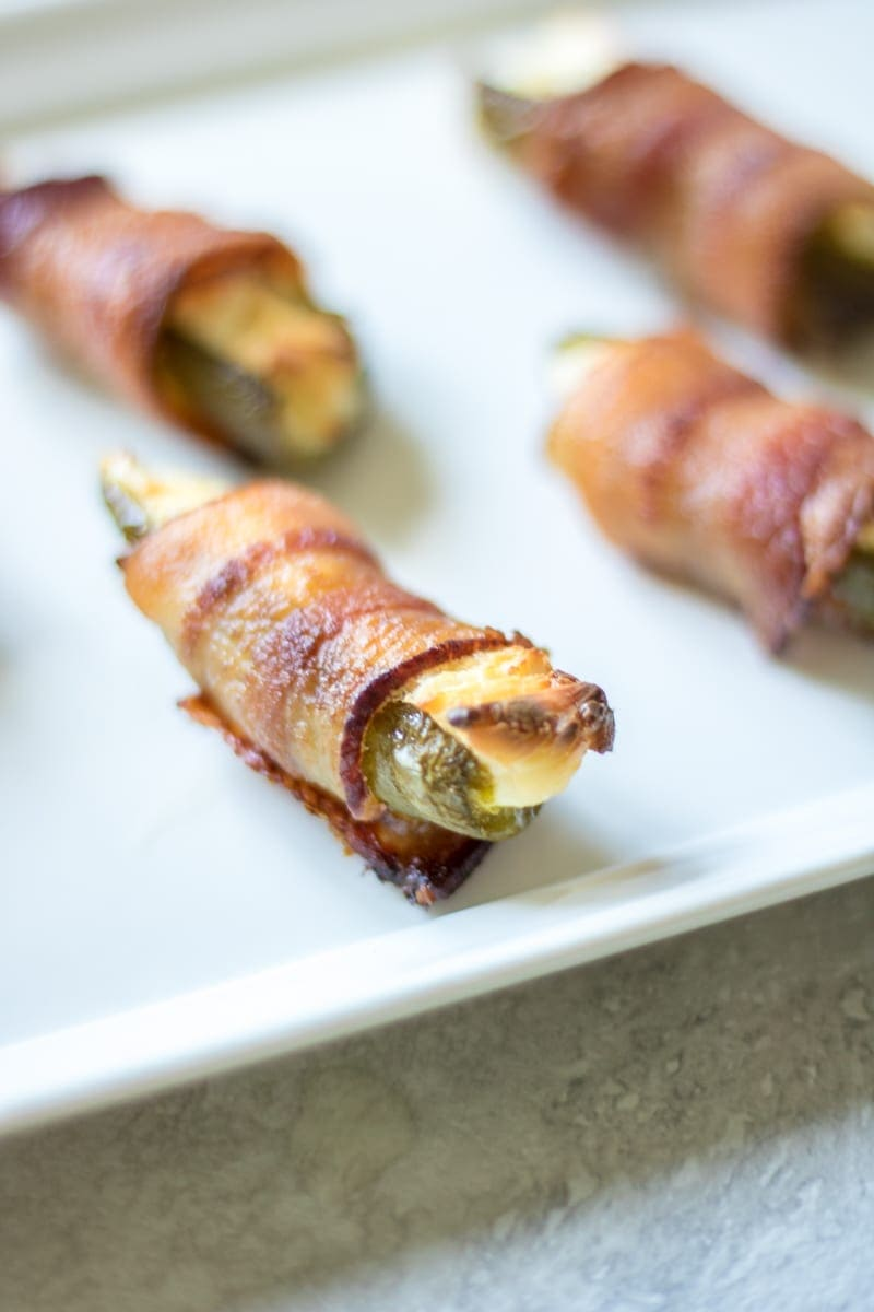 Spicy jalapenos are stuffed with a smoky cream cheese filling, wrapped in bacon, and grilled to perfection for one spicy, creamy bite that is sure to light any appetite on fire!