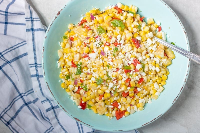 Easy Corn Salsa in a blue bowl topped with feta and cilantro