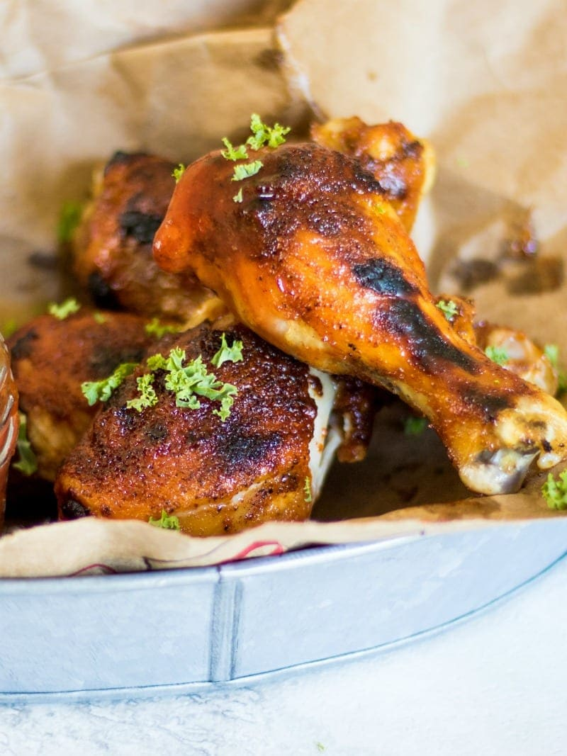 Easy Slow Cooker BBQ Drumsticks in a metal basket lined with brown paper