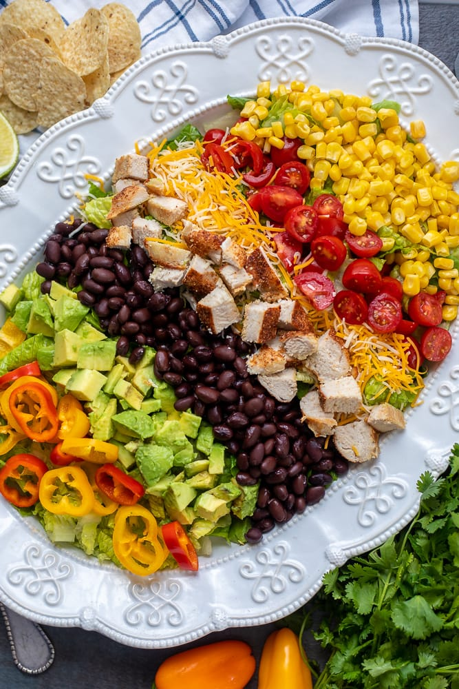 Ingredients for Southwest Chicken Salad Spread out onto white serving platter next to chips
