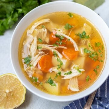 Chicken soup with potatoes and carrots in white bowl next to lemon