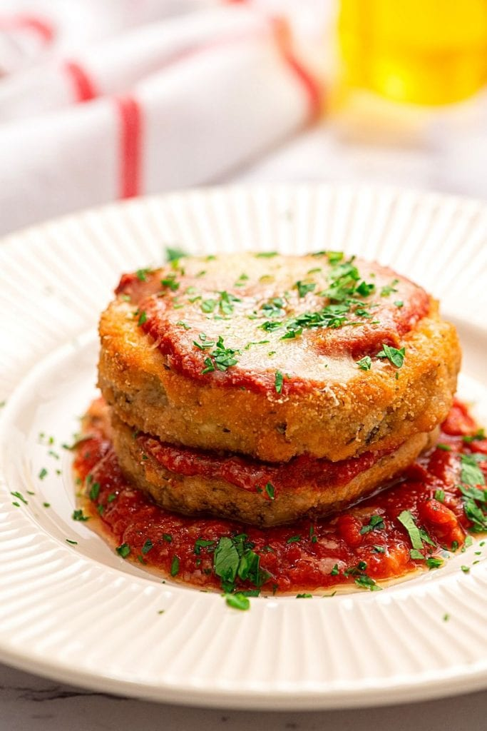 Close up of plated eggplant parmesan on white plate with marinara sauce