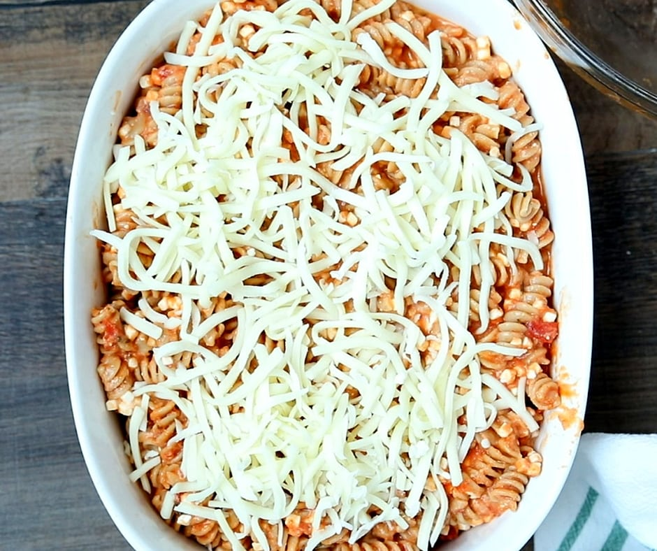 Rotini in casserole dish topped with shredded cheese
