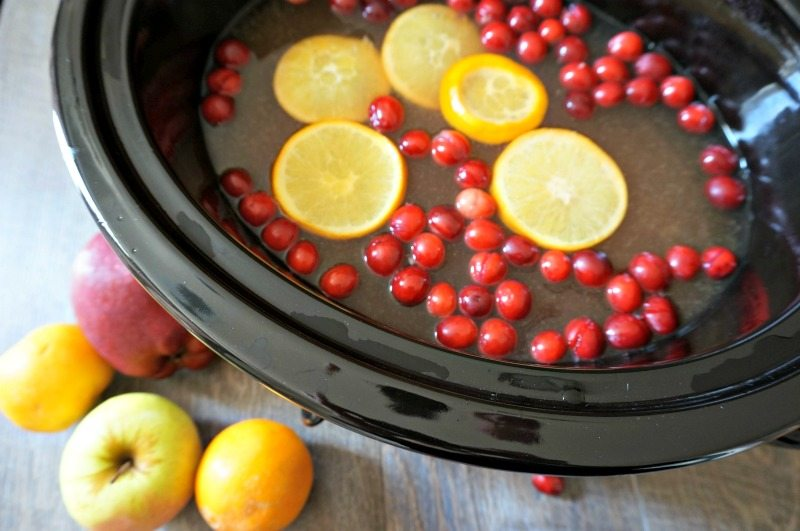 Mulled Apple Cider in slow cooker with fresh oranges and cranberries