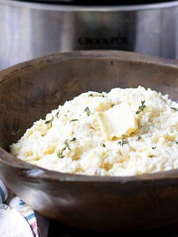 Bowl of Crockpot Mashed Potatoes next to slow cooker