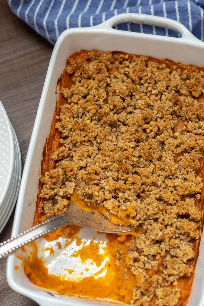 Homemade Sweet Potato Casserole in baking dish with serving spoon to side