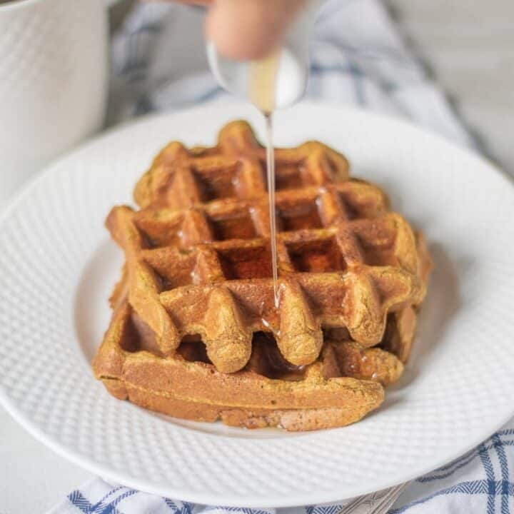 Sweet Potato Waffles on white plate with syrup being poured over waffles