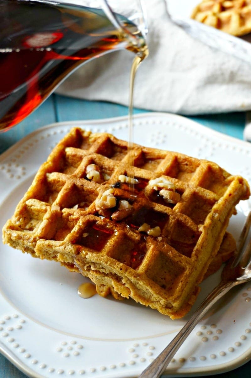 two sweet potato waffles stacked on top of eachother with syrup being poured over them