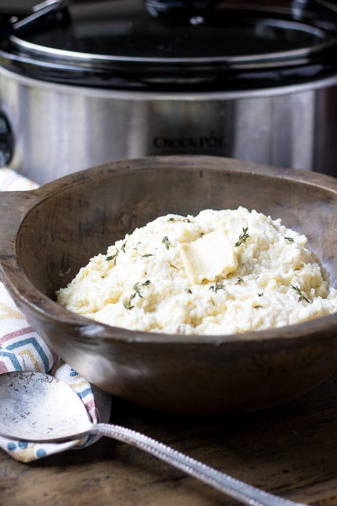 Creamy Parmesan Mashed Potatoes in Wooden Bowl next to Crock Pot