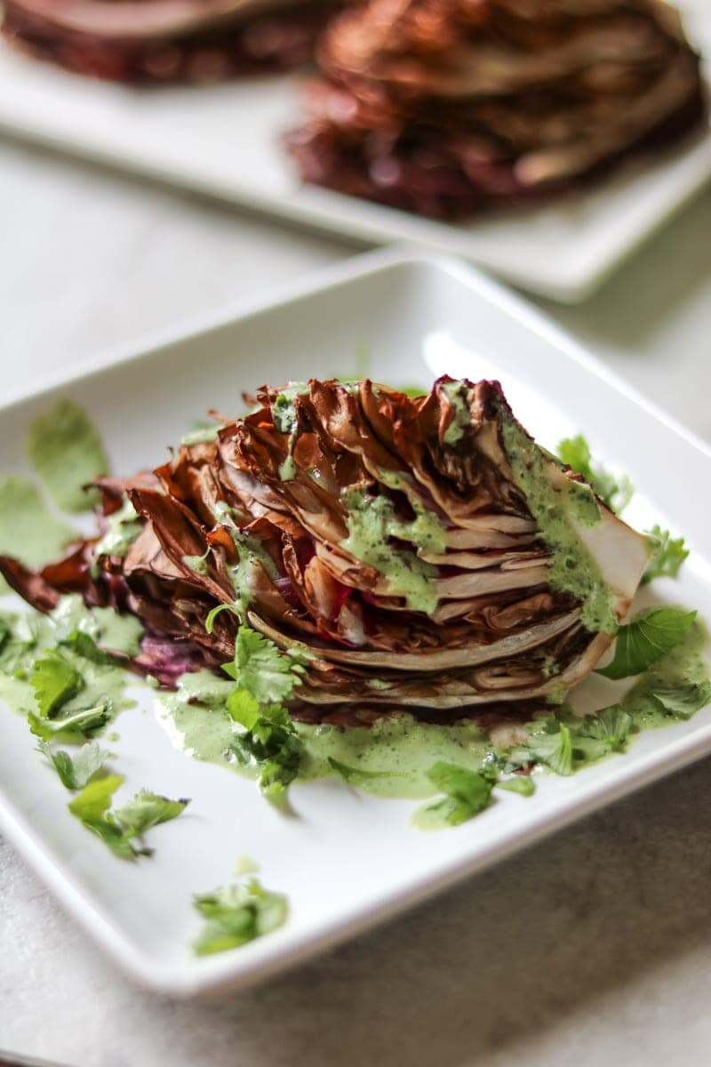Radicchio Wedge Salad with a healthy green goddess dressing on white plate