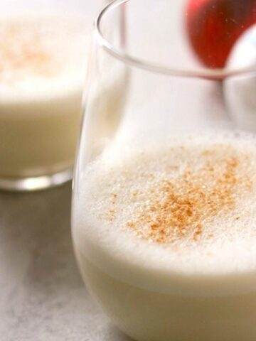 2 glasses of Vegan Eggnog topped with grated nutmeg